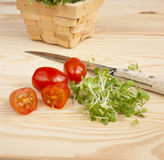Watercress, tomatoes, knife on wooden table Royalty Free Stock Photos