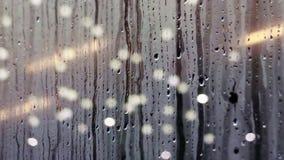 Waterdalingen die neer op vensterglas glijden stock videobeelden