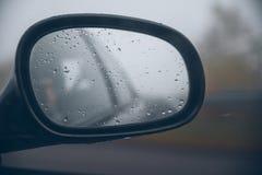 Waterdalingen op autospiegel stock foto's