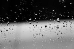 Waterdalingen op de abstracte zwarte donkere achtergrond van de glastextuur Royalty-vrije Stock Fotografie
