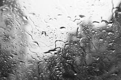 Waterdalingen op de abstracte zwarte donkere achtergrond van de glastextuur Royalty-vrije Stock Foto
