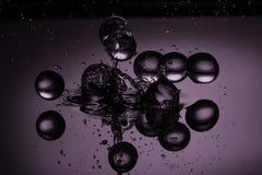 Waterdalingen op een Purpere Achtergrond Stock Fotografie