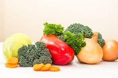 不同的菜和新鲜的草本与waterdrops在白色桌上 橙色切片红萝卜和硬花甘蓝新芽 免版税库存图片