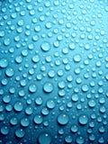Waterdrops op blauw Stock Afbeeldingen