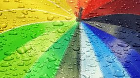 Waterdrops on rainbow coloured parasol. Abstract photo of raindrops on rainbow coloured umbrella ideal for wallpaper background own text etc stock images