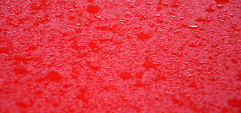 Waterdrops on red metal surface Stock Photo