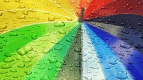 Waterdrops sul parasole colorato arcobaleno immagini stock