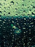 Waterdrops on a window. Waterdrops on a window with a background of green, orange and blue colors royalty free stock photos