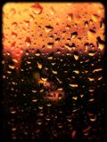 Waterdrops on a window. Waterdrops on a window with a background of green, orange and blue colors stock photo
