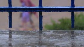 Waterdruppeltjes die met vensters, balkons of traliewerk tegen de achtergrond van de straat druipen waar er regen is stock footage