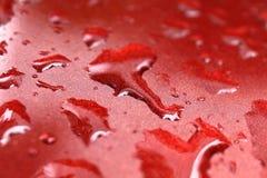 Waterdruppeltjes nat op de rode kap van de auto` s oppervlakte, waterdaling op rode textuur, natte het close-up selectieve nadruk stock afbeeldingen