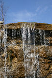 Waterfall 1. The top of a waterfall against a lovely blue sky. This is a man made waterfall as part of the landscaping of this property Stock Photo