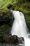Waterfall. Cold and rapid water stream falling down between the stones with green moss Royalty Free Stock Photography