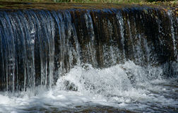 Waterfall. Weir with splashing water and foam Royalty Free Stock Photo