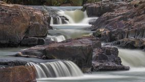 Colorful Waterfall rocky quarry surrounded by green tries and painted rocks stock photography
