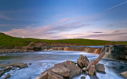 Waterfall. Of Tosna river riffle with quarry spalls in sunset light Royalty Free Stock Photography