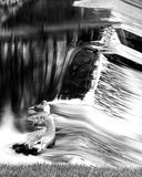 Waterfall. Black and white photo of a log in a waterfall Royalty Free Stock Images
