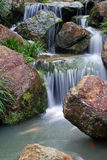 Waterfall. A gentle waterfall surrounded by rocks and grass Royalty Free Stock Images