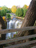 Waterfall. Aerial view with bridge in background and wooden fence and tree in forefront stock photo