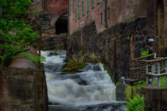 Waterfall through ancient industry buildings. Mölndals Kvarnby. Waterfall through the ancient industry buildings of Mölndals Kvarnby, near Gothenburg in Sweden stock image