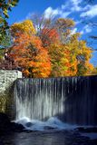 Waterfall in Autumn. Bright autumn trees looking over a waterfall Royalty Free Stock Photos