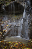 Waterfall with autumn leaves Stock Photography