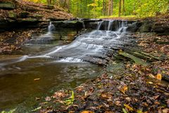 Waterfall In Autumn. One of the many scenic waterfalls along the Sulpher Springs Creek in Bentleyville Ohio during peak fall colors. This small waterfall looks stock image