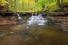 Waterfall In Autumn. One of the many scenic waterfalls along the Sulpher Springs Creek in Bentleyville Ohio during peak fall colors. This small waterfall looks royalty free stock image