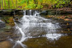 Waterfall In Autumn. One of the many scenic waterfalls along the Sulpher Springs Creek in Bentleyville Ohio during peak fall colors. This small waterfall looks royalty free stock photos