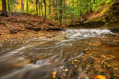 Waterfall In Autumn. One of the many scenic waterfalls along the Sulpher Springs Creek in Ohio during peak fall colors. This small waterfall looks it's best with royalty free stock image
