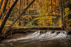 Waterfall In Autumn. One of the many scenic waterfalls along the Sulpher Springs Creek in Ohio during peak fall colors. This small waterfall looks it's best with royalty free stock photography