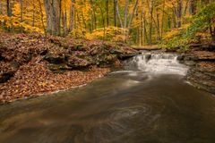 Waterfall In Autumn. One of the many scenic waterfalls along the Sulpher Springs Creek in Ohio during peak fall colors. This small waterfall looks it's best with stock photography