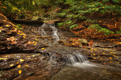 Waterfall In Autumn. One of the many scenic waterfalls along the Sulpher Springs Creek in Ohio during peak fall colors. This small waterfall looks it's best with royalty free stock photos