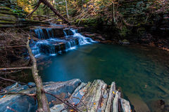 Waterfall in autumn on a small stream near Ithaca, NY. A deep pool formed by a waterfall holds trout Royalty Free Stock Photo