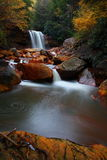 Waterfall in Autumnal forest. Scenic view of waterfall in Autumnal forest with slow motion blur Stock Photos