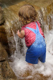 Waterfall baby. Toddler in overalls playing in a waterfall stock photography