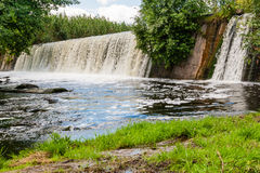 Waterfall on a background of green grass and blue sky Stock Image