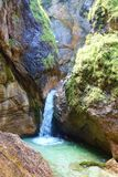 Waterfall with a crystal clear water flowing in Almbach gorge near Berchtesgaden in Eastern Germany, Europe. Waterfall with bare rocks in Almbach gorge near royalty free stock photos
