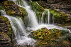 Waterfall. Beautiful motion blurred waterfall flowing from mossy rocks Royalty Free Stock Images