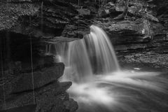Waterfall behind the Rock. In black and white located at Bozenkill Preserve Scoharie New York royalty free stock photos