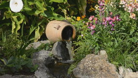 Waterfall and birdsong. Garden feature, small waterfall,  background of birdsong. Colourful flowers