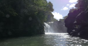 Waterfall and black volcanic rocks in Mauritius