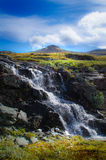 Waterfall and blue sky. Close up photo of a waterfall in Norway stock images