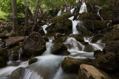 Waterfall blur over rocks. Blur of moving waterfall flowing over rocks in forest stock photos