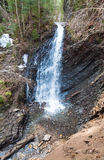 Waterfall and brook in mountain forest ravine Stock Photos