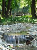Waterfall on the brook under the bridge. Ideal place for rest when you can hear splash of the falling water Royalty Free Stock Photo
