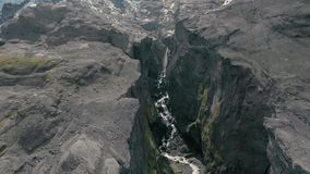 Canyon Aerial View. Waterfall or canyon dweller, hidden between an opening in cliffs in Iceland. Gushing water glimpsed through canyon entrance, moss covered stock video footage