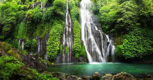 Waterfall Cascade in Green Jungle. Hidden jungle waterfall cascade in tropical rainforest with rock and turquoise blue pond. Its name Banyumala because its twin royalty free stock image