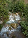 Waterfall cascades down the mountain side over moss covered rocks amid the trees and bushes stock photo