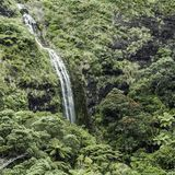 Waterfall cascading down a mountain in green surroundings Royalty Free Stock Photos